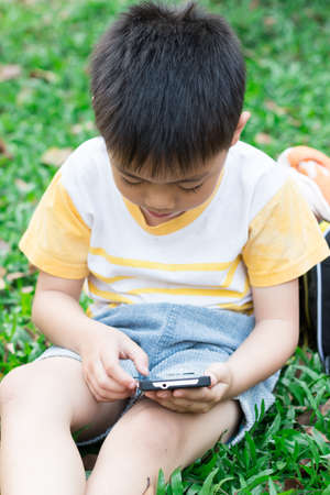 Asian boy playing on mobile phone  photo