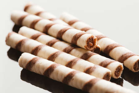 filled roll: wafer rolls with nut filling on a mirrored background.