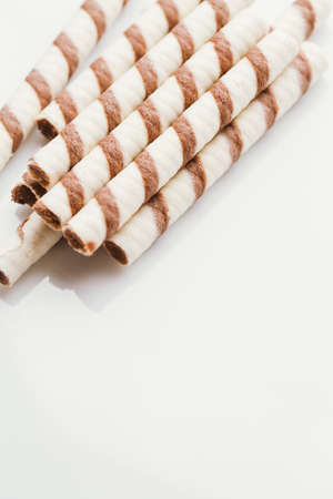 hazelnuts: wafer rolls with nut filling on a light mirror background.