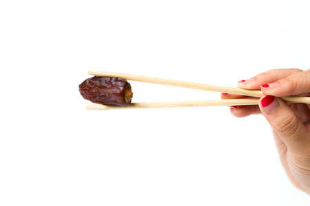 A woman hand hold a dates using chop sticks isolated over shite background