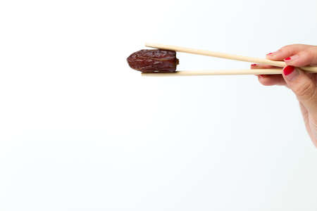 chop sticks: A woman hand hold a dates using chop sticks isolated over shite background