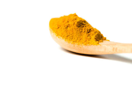 herbaceous: A turmeric powder in a wooden spoon isolated white background