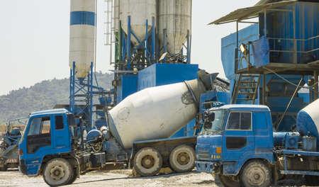 batch: Concrete mixer trucks get loaded at portable batch plant Stock Photo