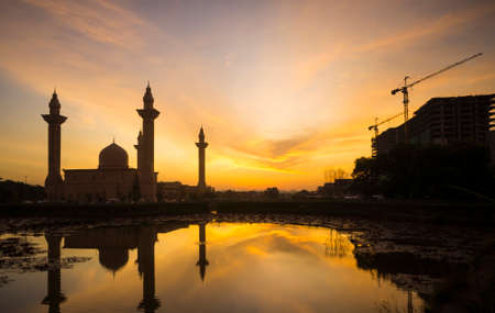 islamic wonderful: Silhouette of the Tengku Ampuan Jemaah Mosque, Bukit Jelutong, Malaysia mosque  and building under construction at sunrise