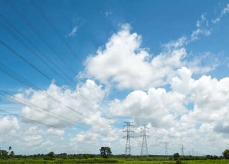 megawatt: Power line transmittion and pylon over the field with nice blue and bright sky Stock Photo