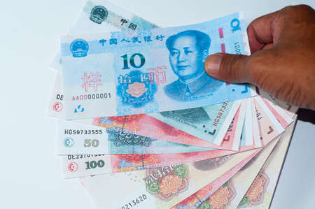 A man holding Yuan notes from China's currency. Chinese banknotes.