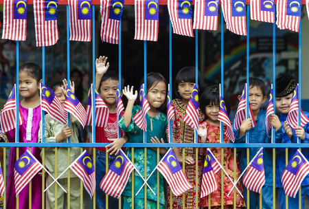 MALACCA, MALAYSIA - AUGUST 27, 2010: Kids with Malaysia flag Jalur Gemilang. Editorial
