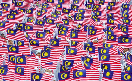 KUALA LUMPUR, MALAYSIA - AUGUST 28, 2014: Student hold Malaysia flag 'Jalur Gemilang' during rehearsal of Independent Day celebration in Kuala Lumpur.