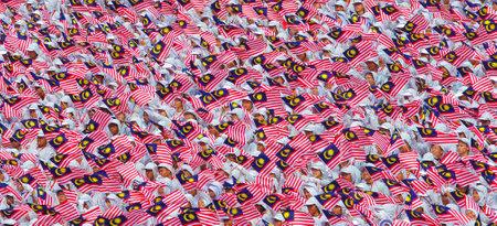 1malaysia: KUALA LUMPUR, MALAYSIA - AUGUST 31, 2014: Student waving Malaysia flag Jalur Gemilang during Independent Day celebration in Kuala Lumpur.