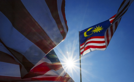 conjunction: Malaysia flag also known as Jalur Gemilang wave with the blue sky. Every year in August the government of Malaysia urged people to fly the flag in conjunction with the Independence Day celebration or Merdeka Day. Stock Photo