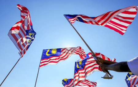1malaysia: Hand waving Malaysia flag also known as Jalur Gemilang against the blue sky. Every year in August the government of Malaysia urged people to fly the flag in conjunction with the Independence Day celebration or Merdeka Day.