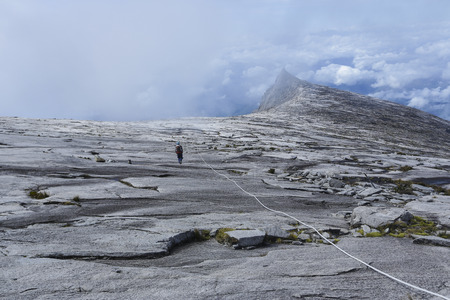 lows: Climbers walk down the Lows Peak to the South Peak (3,921m) of Mount Kinabalu, Sabah, Malaysia. Mount Kinabalu or Gunung Kinabalu is the 20th most prominent mountain in the world by topographic prominence. Stock Photo