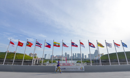 KALLANG, SINGAPORE - MAY 30, 2015 : A boy walk across the national flags of Southeast Asia countries; Brunei Darussalam, Myanmar / Burma, Cambodia, Indonesia, Laos, Malaysia, Philippines, Singapore, Thailand, Vietnam, East Timor. Stock Photo - 64954390