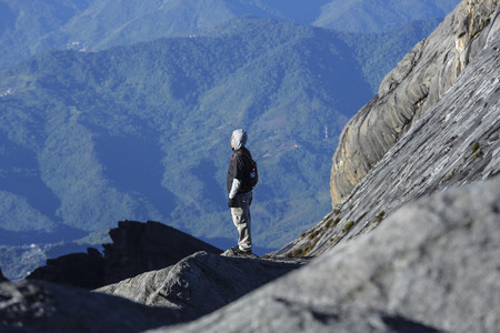 lows: SABAH, MALAYSIA - AUGUST 23, 2014 : Climbers relax while taking a breath after reaching the Lows Peak (4095m) summit of Mount Kinabalu, Sabah, Malaysia. Mount Kinabalu or Gunung Kinabalu is the 20th most prominent mountain in the world by topographic pro