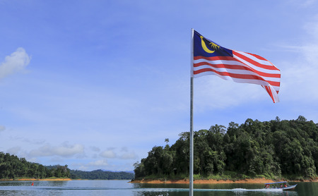 Malaysia Flag, Jalur Gemilang waving with the background of boat at the lake and Malaysian rainforest trees.