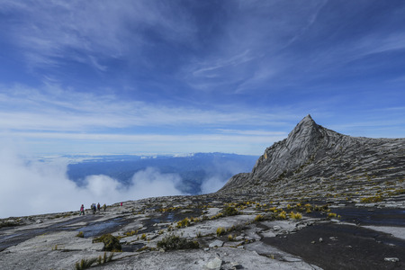 lows: Climbers walk down the Lows Peak across the South Peak (3,921m) of Mount Kinabalu, Sabah, Malaysia.  Mount Kinabalu or Gunung Kinabalu is the 20th most prominent mountain in the world by topographic prominence. Stock Photo