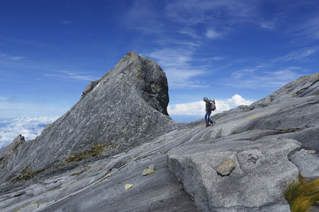 lows: RANAU, MALAYSIA - AUGUST 23, 2014 - Climbers walk down the Lows Peak (4095m) across the St. John Peak (4090m) of Mount Kinabalu, Sabah, Malaysia. Mount Kinabalu or Gunung Kinabalu is the 20th most prominent mountain in the world by topographic prominence