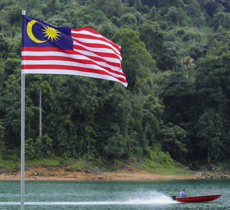 1malaysia: Malaysia Flag, Jalur Gemilang waving with the background of boat at the lake and Malaysian rainforest trees.