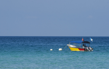 Boat at crystal clear waters Perhentian Kecil Island beach, Terengganu, Malaysia. Stock Photo