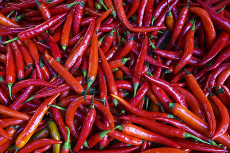 Stack of fresh Red Chili Pepper on display at market.