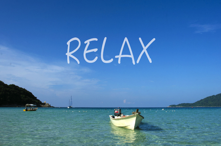 RELAX word with crystal clear waters beach  island at background. Stock Photo
