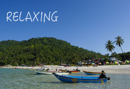 RELAXING word with crystal clear waters beach  island at background.