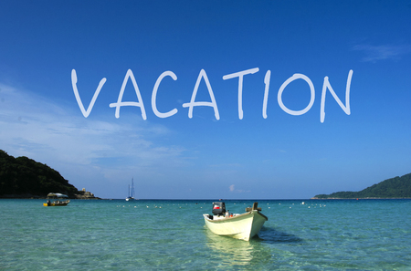 VACATION word with crystal clear waters beach  island at background.