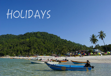 HOLIDAYS word with crystal clear waters beach  island at background.