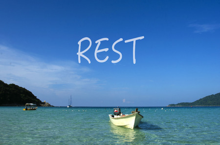 REST word with crystal clear waters beach  island at background.