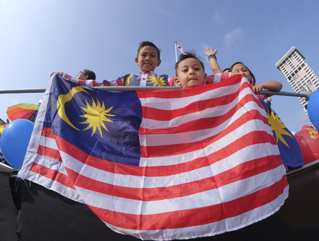 1malaysia: KUALA LUMPUR, MALAYSIA - AUGUST 31, 2016 : Kids waving Malaysia flag also known as Jalur Gemilang during Independence Day celebration or Merdeka Day at Merdeka Square. Editorial