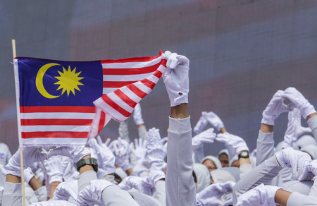 1malaysia: Performers waving Malaysia flag also known as Jalur Gemilang during Independence Day celebration or Merdeka Day at Merdeka Square.