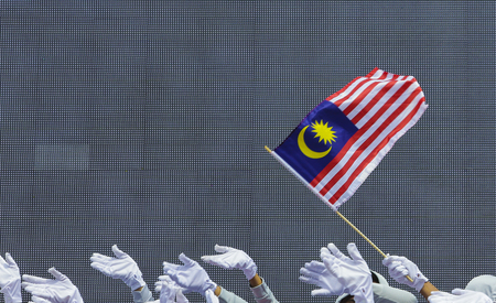 Performers waving Malaysia flag also known as Jalur Gemilang during Independence Day celebration or Merdeka Day at Merdeka Square.