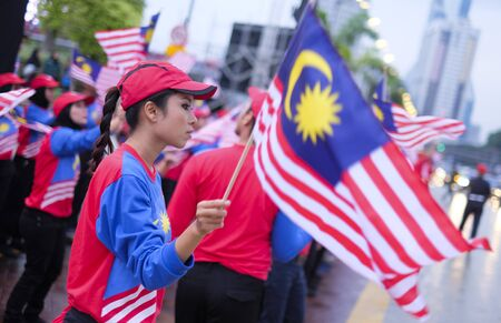 KUALA LUMPUR, MALAYSIA - AUGUST 31, 2016 : Performers waving Malaysia flag also known as Jalur Gemilang during Independence Day celebration or Merdeka Day at Merdeka Square.