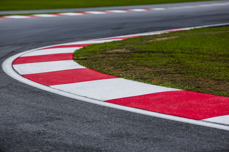 Curving asphalt red and white kerb of a race track detail. Motorsports racing circuit close up.