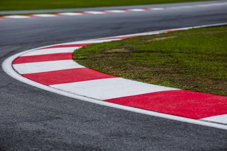 Curvando la acera roja y blanca del asfalto de un detalle de la pista de carreras. Circuito de carreras de automovilismo de cerca.