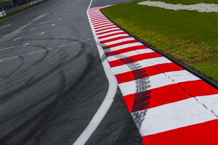 Asfaltowy czerwono-biały krawężnik z detalem toru wyścigowego ze śladami opon. Tor wyścigowy sportów motorowych z bliska. Zdjęcie Seryjne