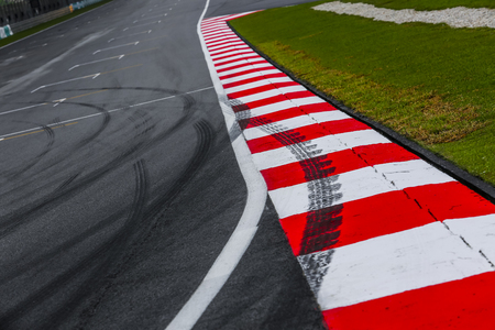 Asphaltieren Sie rote und weiße Kandare eines Rennstreckendetails mit Reifenkennzeichen. Motorsport-Rennstrecke hautnah. Standard-Bild