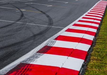●タイヤマーク付きのレーストラックディテールのアスファルト赤と白の縁石。モータースポーツレーシングサーキットクローズアップ。