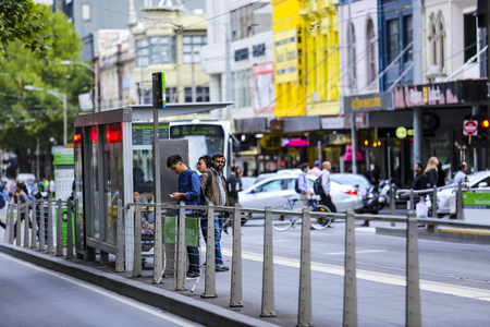 MELBOURNE, AUSTRALIA - MARCH 15, 2018 : People wait for Tram in Melbourne city center. Melbourne has the largest urban tramway network in the world. One of tourist attraction.