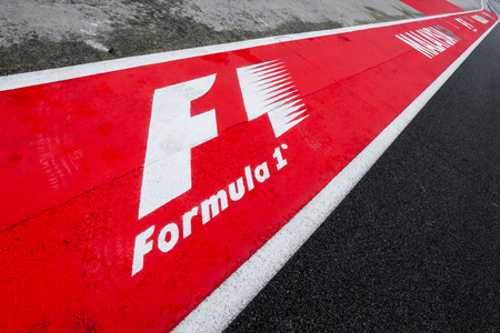 SEPANG, MALAYSIA : SEPTEMBER 28, 2017 : Formula One (F1) logo on asphalt red and white of a race track. Motorsports racing circuit close up.