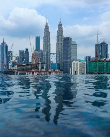KUALA LUMPUR, MALAYSIA - JULY 18, 2018 : Swimming pool with background view of Petronas Twin Tower and Kuala Lumpur city centre skyline.
