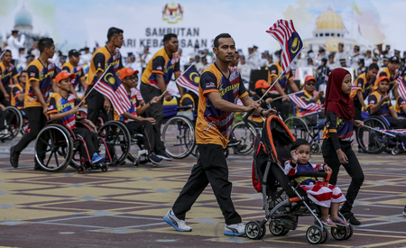 PUTRAJAYA, MALAYSIA - AUGUST 31, 2018 : Participant waving Jalur Gemilang flag during National Day celebration parade in Putrajaya. Celebrating the 61th anniversary of independence or Merdeka Day.