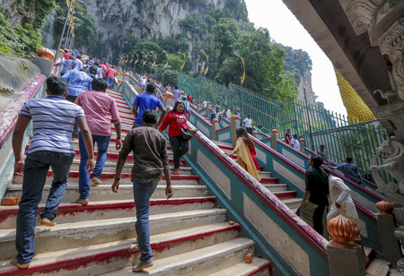 KUALA LUMPUR, MALAYSIA - OCTOBER 18, 2017 : Indian & tourist at entrance steps to Batu Caves temple in Kuala Lumpur. Batu Caves is a an iconic and popular tourist attraction in Malaysia. Редакционное