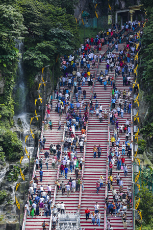 KUALA LUMPUR, MALAYSIA - OCTOBER 18, 2017 : Indian & tourist climb steps to Batu Caves temple in Kuala Lumpur. Batu Caves is a an iconic and popular tourist attraction in Malaysia.