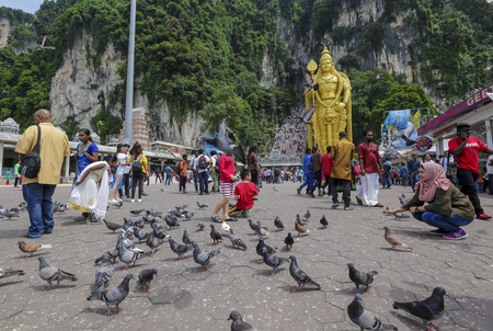 KUALA LUMPUR, MALAYSIA - OCTOBER 18, 2017 : People at entrance of Batu Caves temple in Kuala Lumpur. Batu Caves is a an iconic and popular tourist attraction in Malaysia. Редакционное