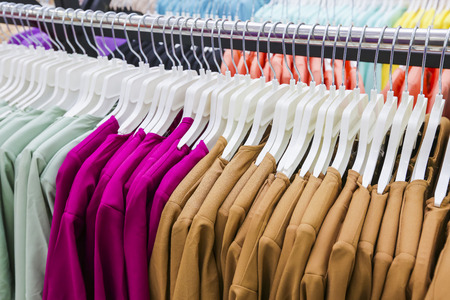 Clothes hang on a shelf in a store. Variety of choice. Stok Fotoğraf