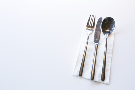 Fork, Spoon and Table Knife on the white table background at restaurant  cafe.