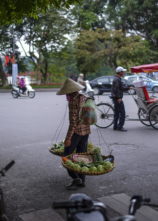 """Vietnamese street market lady seller. They carrying a """"quang ganh"""" (two baskets slung from each end of a wooden or bamboo pole) filled up with food."""