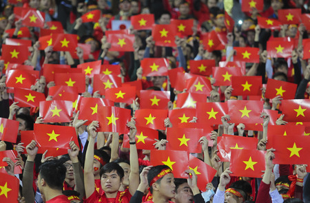 HANOI, VIETNAM - DECEMBER 11, 2014 : People of Vietnam waving their flag.