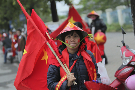 HANOI, VIETNAM - DECEMBER 11, 2014 : A woman painted Vietnam flag on her face to show patriotism to the country.